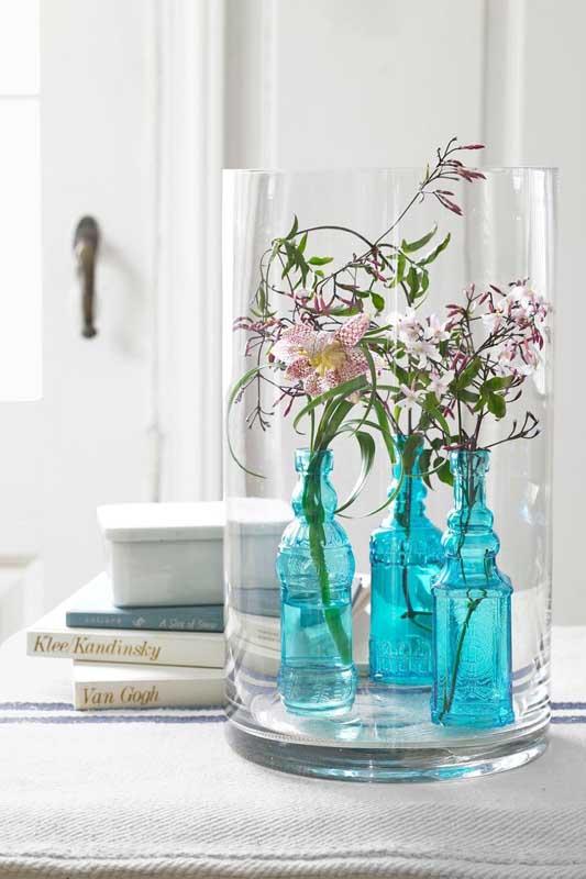 Que tal garrafas de vidro pintadas de azul para serem usadas como vasinho? Repare que elas foram colocadas dentro de um recipiente maior também de vidro
