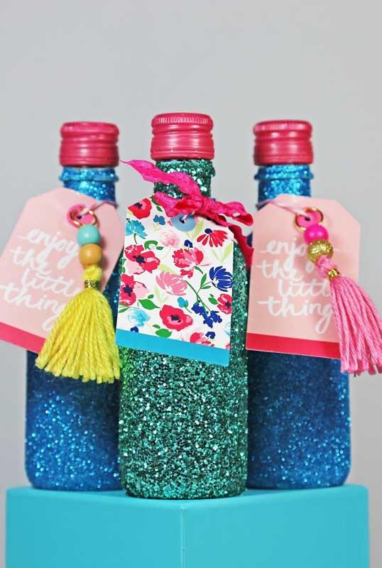 Garrafas decoradas com glitter para serem distribuídas como lembrancinha de festa