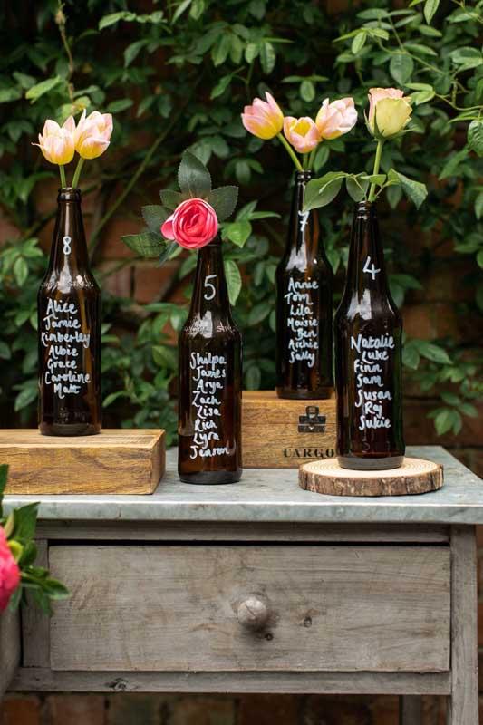 Anota essa ideia: garrafas de vidro com o nome dos convidados para colocar no centro de mesa!