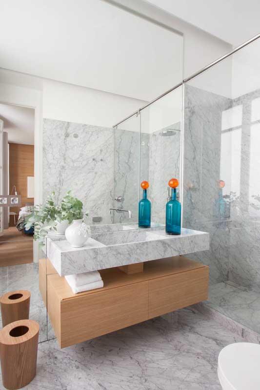 A decoração neutra do banheiro ganhou vida com a presença da garrafa azul e sua tampa laranja