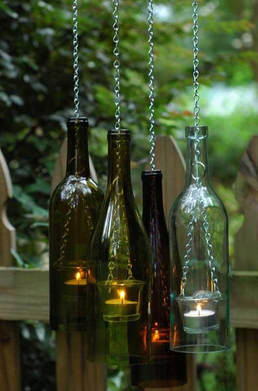 Pendentes feitos com garrafas de vidro. Repare que a base da garrafa foi cortada para inserir as pequenas velas