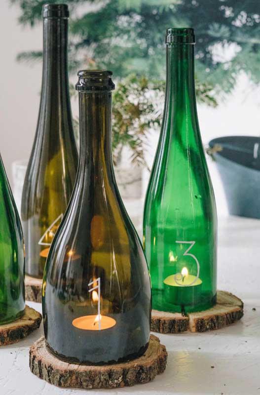 Luminárias feitas com garrafa para serem usadas como centro de mesa em festas. Destaque para a base feita com tronco de árvore