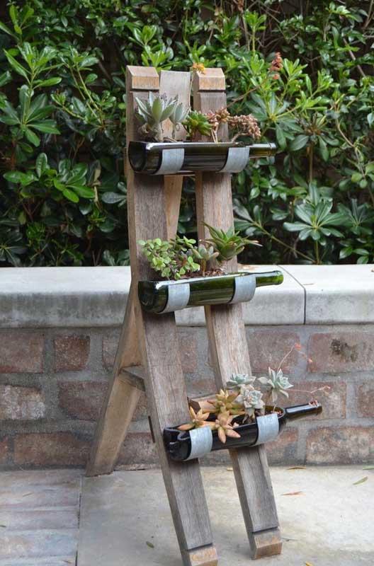 Já aqui a decoração com garrafas de vinho virou suporte para as suculentas