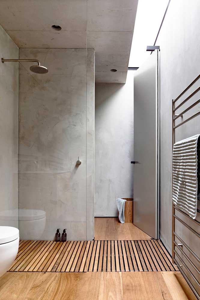 Piso de madeira em toda extensão do banheiro, incluindo o box