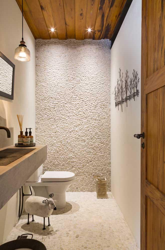 Já aqui, os seixos servem tanto como piso para o banheiro, quanto para o revestimento da parede