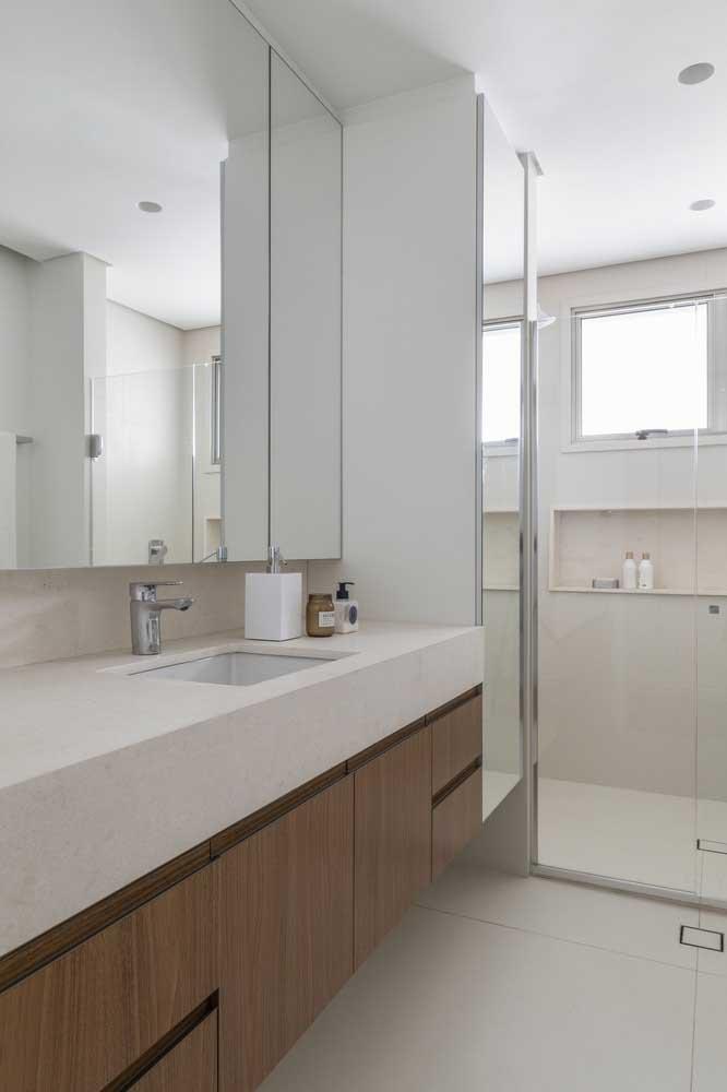 Porcelanato bege para o piso do banheiro. A bancada de madeira confere o conforto