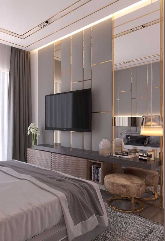 Quarto de casal de luxo pequeno com destaque para o painel de espelhos que recebe a televisão. O uso do dourado é outro trunfo por aqui
