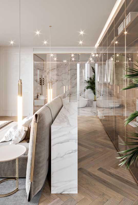 Quarto de casal de luxo com closet. Destaque para o uso do mármore, do vidro e da iluminação feita por luminárias suspensas
