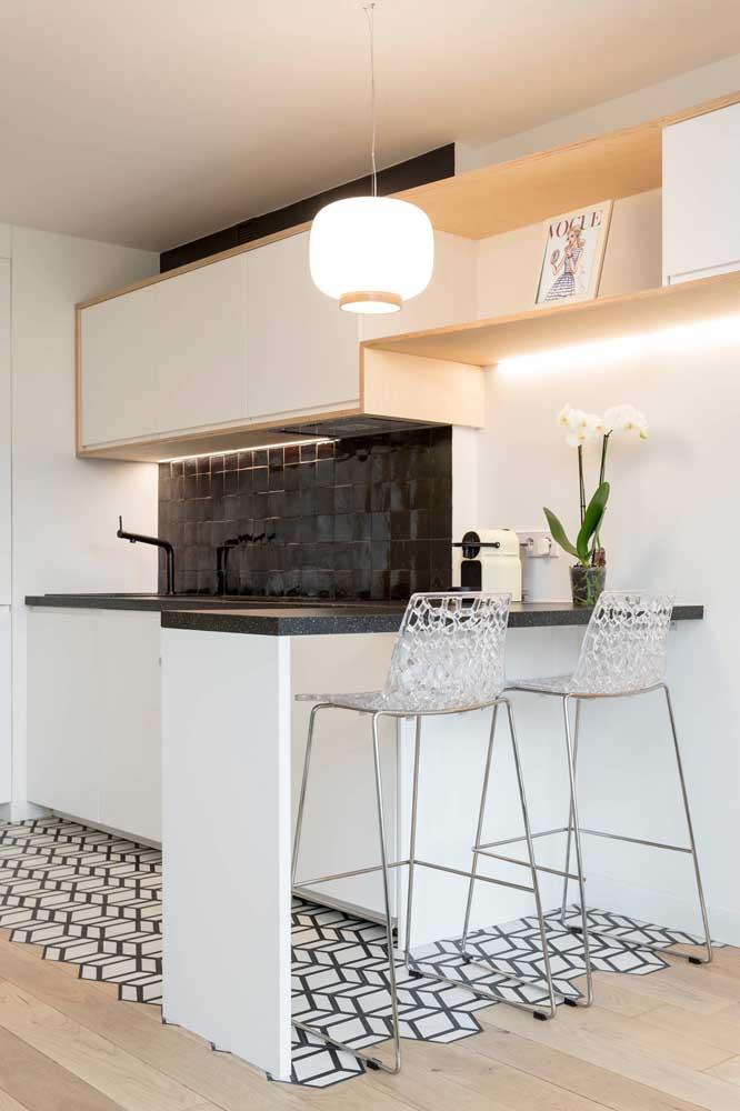 Cozinha branca com azulejos pretos. No chão, o piso segue a mesma padronagem de cores