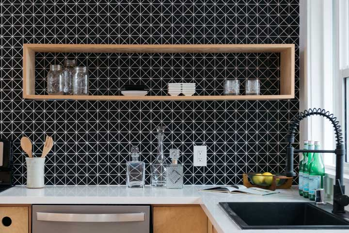 Azulejo preto com linhas brancas. A presença marcante das peças faz com que apenas uma das paredes receba o revestimento