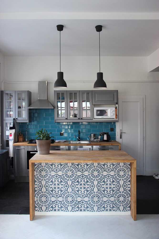 Composição de azulejos azuis para cozinha moderna. Aos fundos, a opção foi pelo azulejo de metrô, já na bancada se destacam os azulejos estilo português