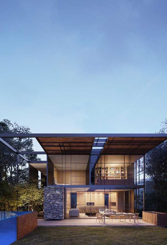 Fachada de casa moderna com paredes de vidro. Destaque para as linhas retas que garantem o tom moderno da construção