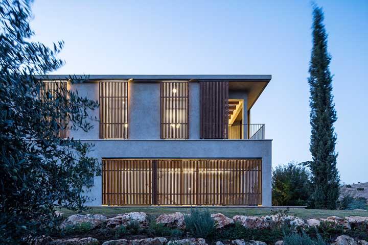 Os painéis de madeira na fachada garantem um toque de conforto para a casa moderna