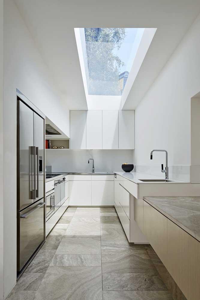 O vão no telhado permite que a cozinha da casa moderna ganhe luminosidade natural