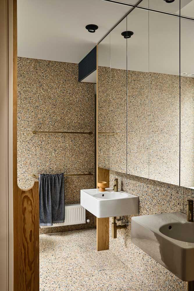 Nesse banheiro, o granilite é o grande destaque. Repare ainda como ele se harmoniza com as peças douradas