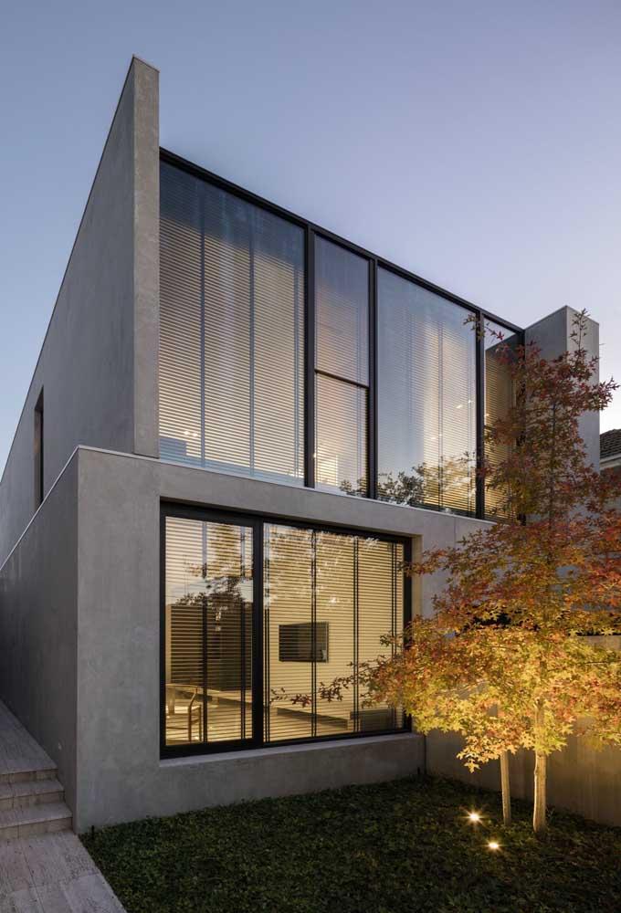 Fachada de casa moderna com pequeno jardim iluminado