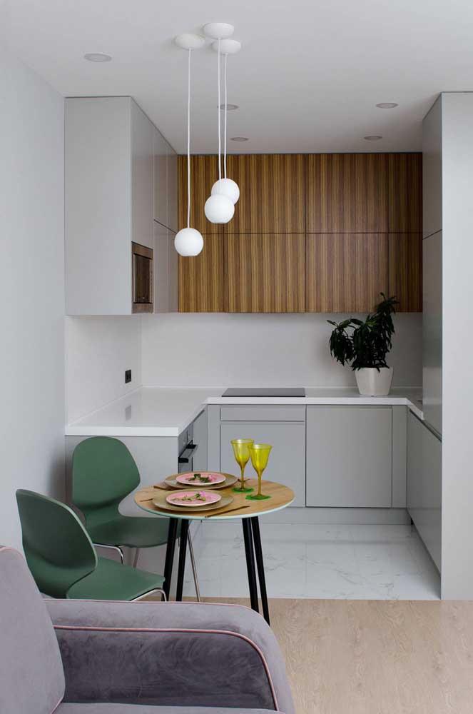 Cozinha planejada para apartamento pequeno com portas sem puxadores. Destaque para o uso da madeira que deixa o projeto mais aconchegante
