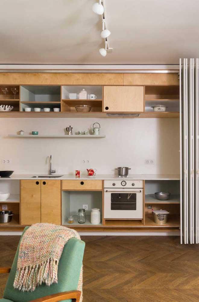 Cozinha planejada em estilo retrô. Repare que a porta sanfonada permite esconder o ambiente quando for necessário