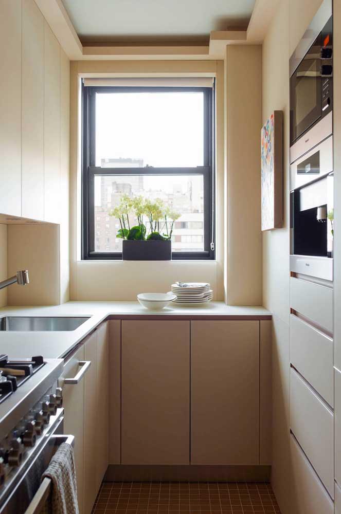 Cozinha planejada para apartamento pequeno em estilo corredor. A ausência de puxadores torna o projeto mais funcional