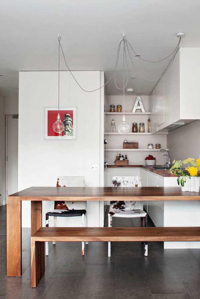 Cozinha planejada para apartamento pequeno integrada com a sala de jantar. Destaque para o uso da madeira