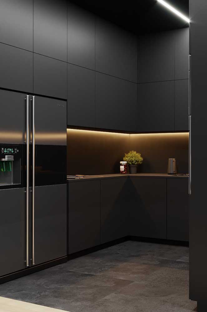 Cozinha planejada preta para apartamento pequeno. O pé direito alto contribui para o uso da cor