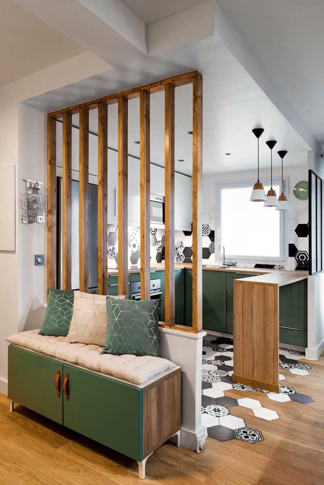 Cozinha planejada para apartamento pequeno em U. A integração com a sala de estar é parcialmente coberta pela divisória vazada