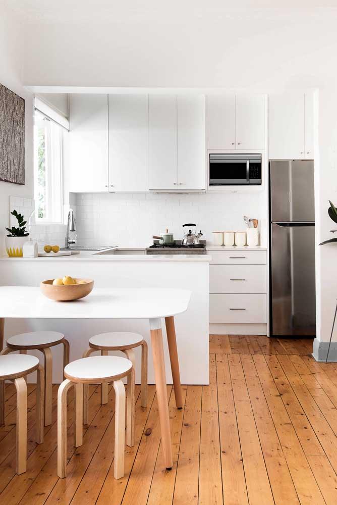 Aqui, o piso de madeira se tornou a base perfeita para a cozinha planejada branca