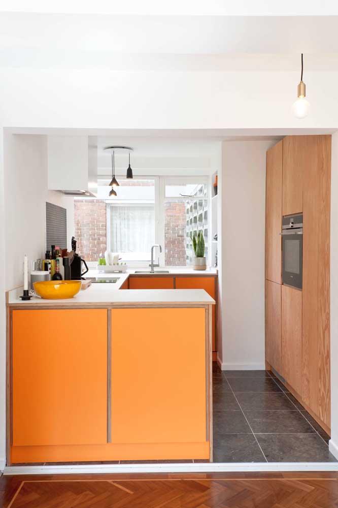 Cozinha planejada para apartamento pequeno com um balcão laranja que dispensa comentários