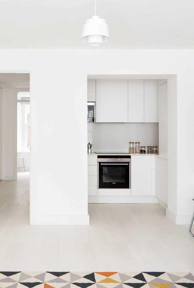 Cozinha planejada branca para apartamento pequeno. A cor clara confere uma maior sensação de espaço