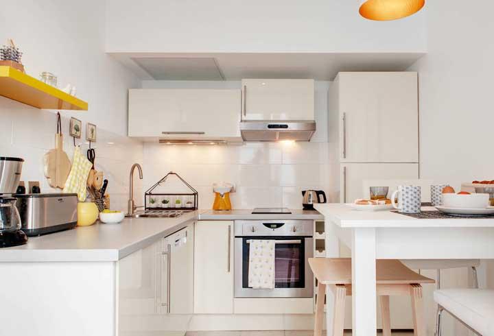 Cozinha planejada para apartamento pequeno com mesa de jantar