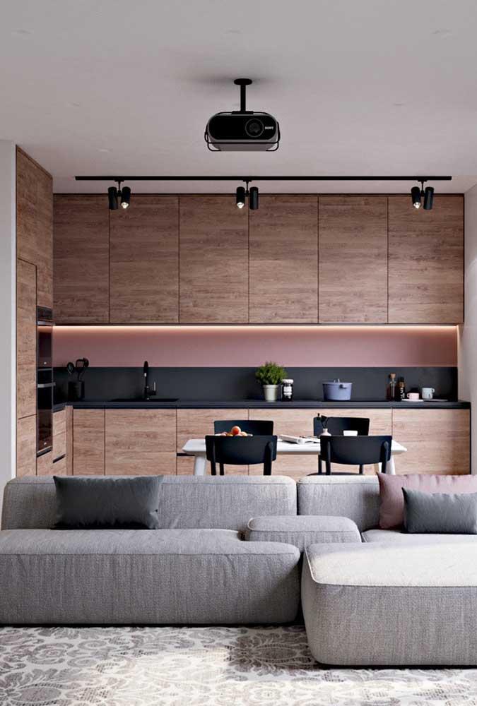 Cozinha planejada para apartamento pequeno integrada com a sala de estar. Destaque para o projeto de iluminação que valoriza os ambientes
