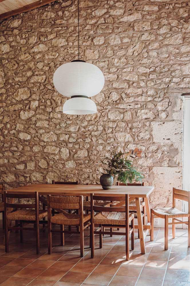 Sala de jantar com decoração rústica contrastada pela luminária branca