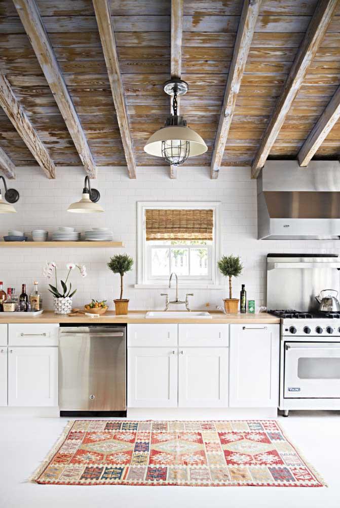 Cozinha rústica branca com destaque para o uso da patiná no teto