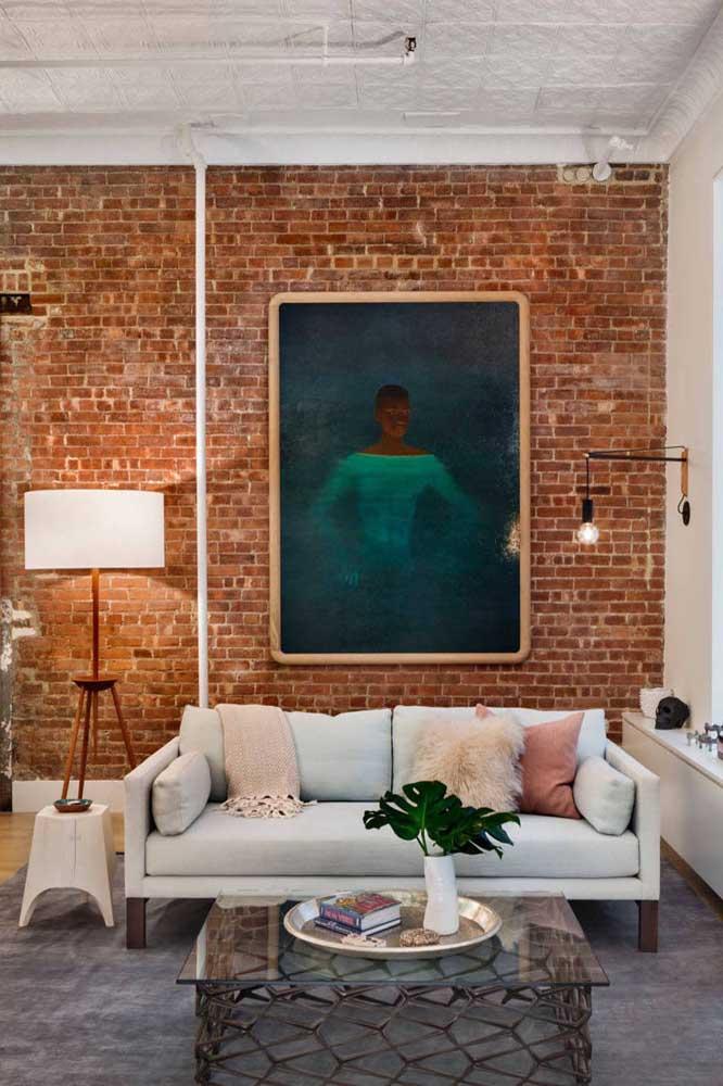 Luminária na parede e no chão. Ambas ajudam a valorizar a parede de maior destaque da sala de estar
