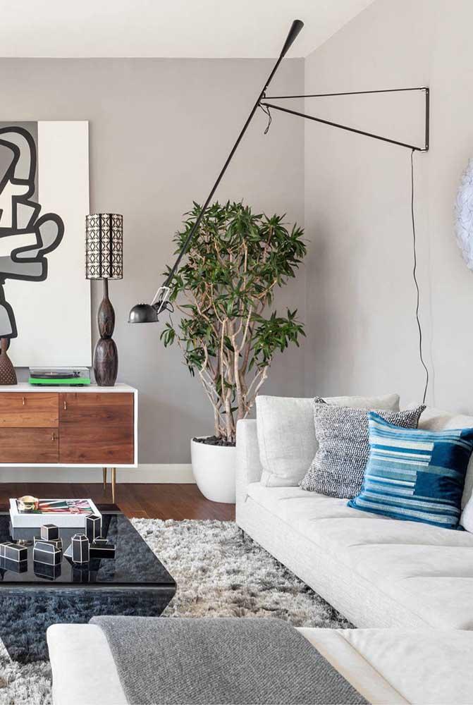 Luminária para sala de parede totalmente direcionável graças ao braço articulado que se estende sobre o sofá
