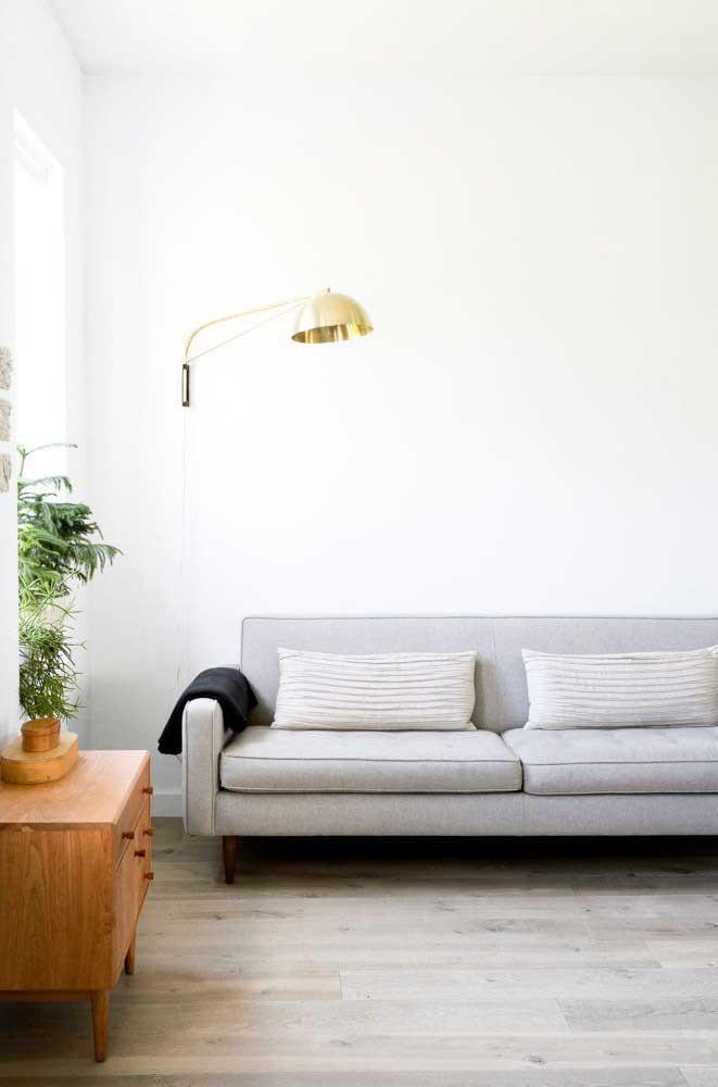 Já aqui, a sala de estar minimalista apostou em uma luminária de chão com detalhes dourados