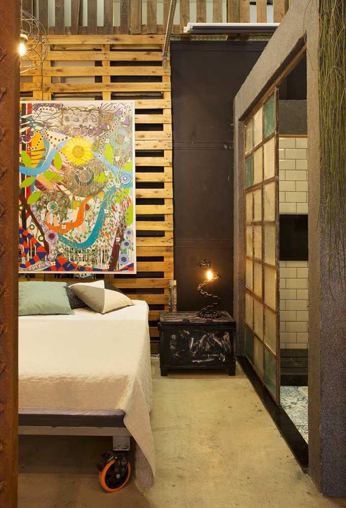 Nesse quarto jovial é o painel de pallets que dá a base para o quadro colorido e abstrato