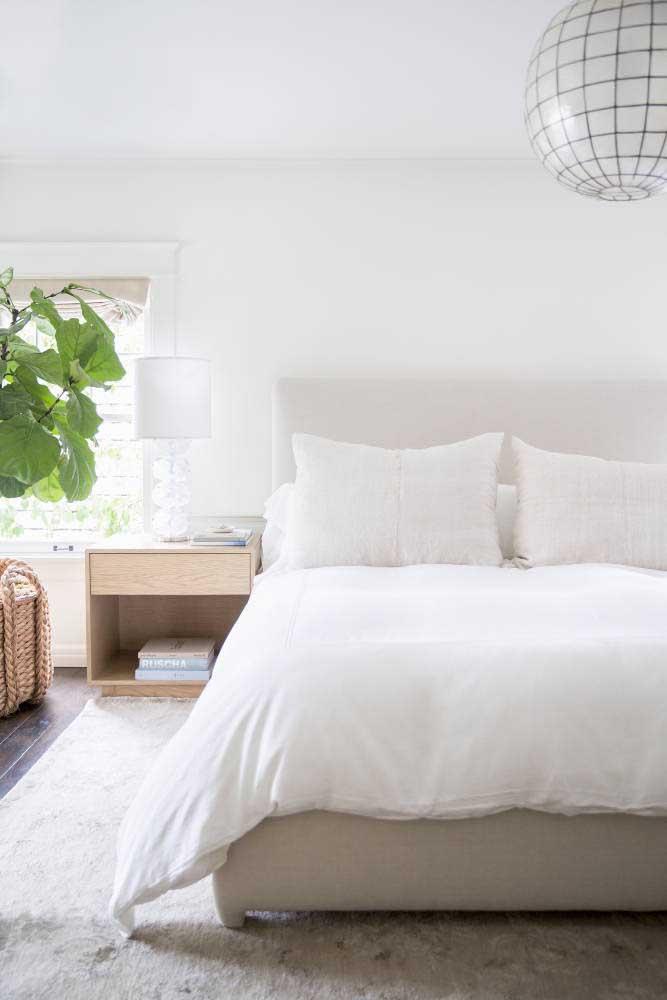 Quarto de casal branco valorizado pelas texturas naturais dos objetos