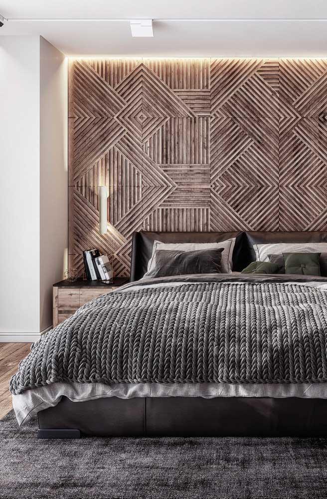 Nesse quarto de casal, o toque de cor fica por conta do painel de madeira e da roupa de cama
