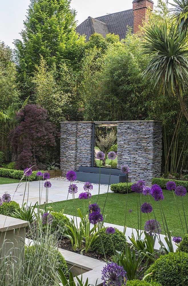Decoração de jardim com flores e uma pequena cascata em meio ao muro de pedras