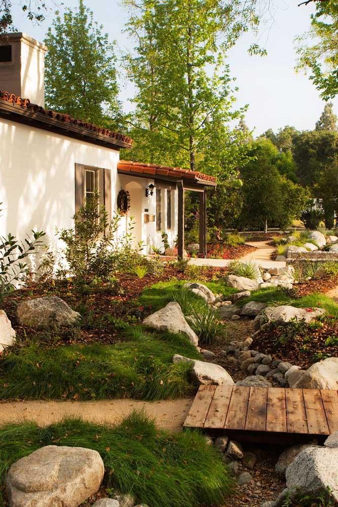 Decoração de jardim rústico com pedras e mini ponte de madeira