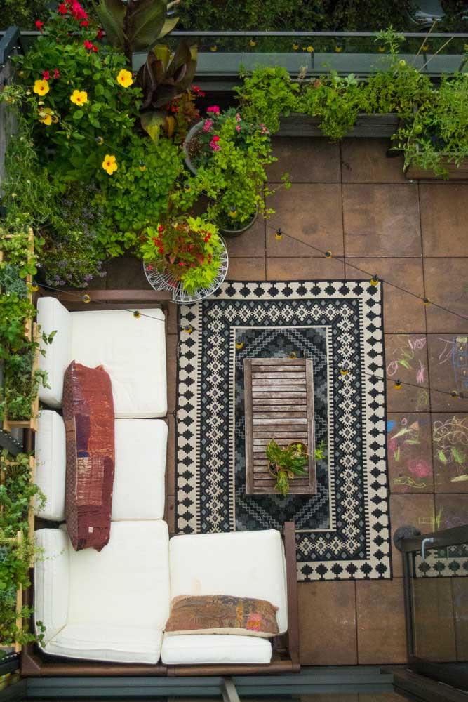 Decoração de jardim na varanda com direito a sofá, tapete e varal de luzes