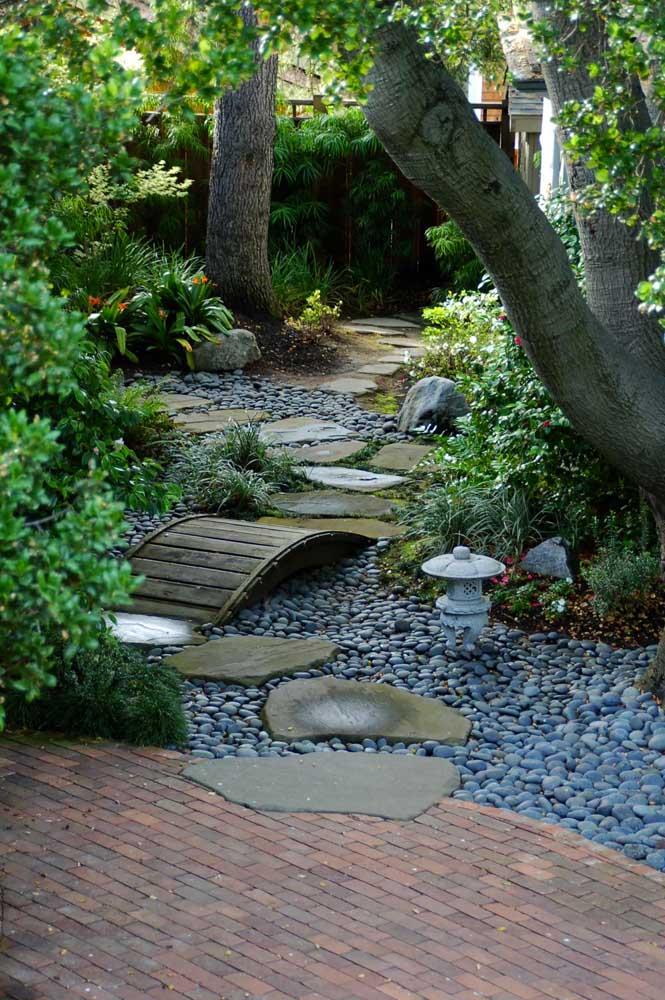 Decoração de jardim de estilo oriental. Destaque para as pedras, a mini ponte e a lanterna