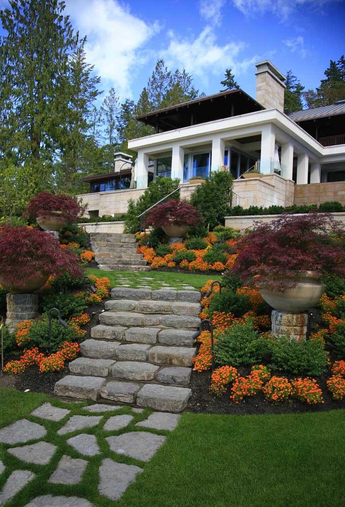 Decoração de jardim clássico com flores e vasos monumentais acompanhando todo caminho da entrada