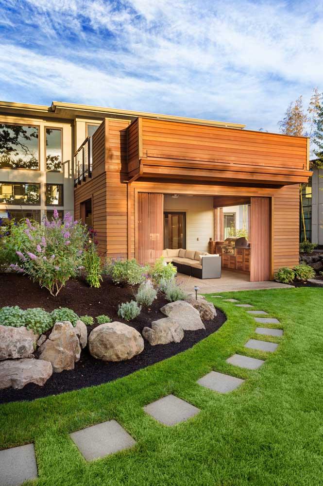 Jardim na entrada da casa decorado com pedras, gramas e placas de cimento