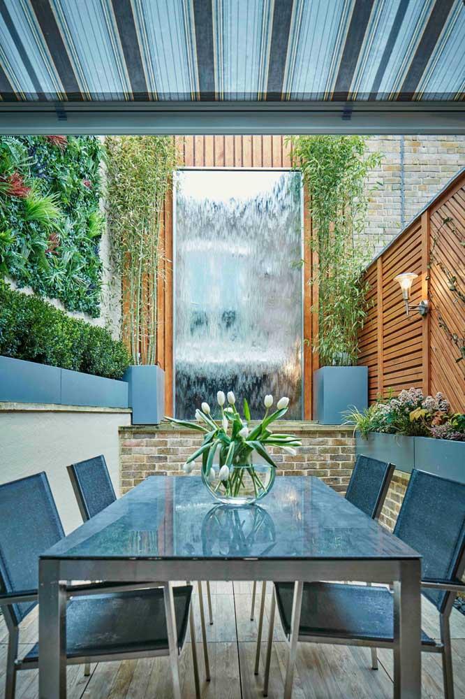 A cascata de água forma um painel vivo na parede da área externa, complementando a decoração do jardim vertical