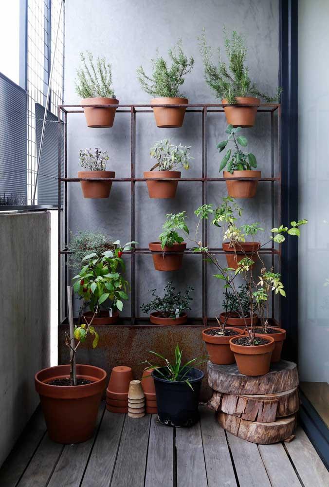 Mini jardim vertical que mistura a estrutura moderna com a rusticidade dos vasos de barro