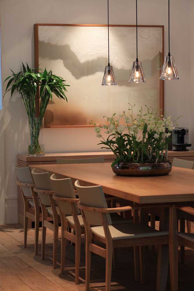 O trio de luminárias pendentes valoriza o arranjo de orquídeas sobre a mesa de jantar