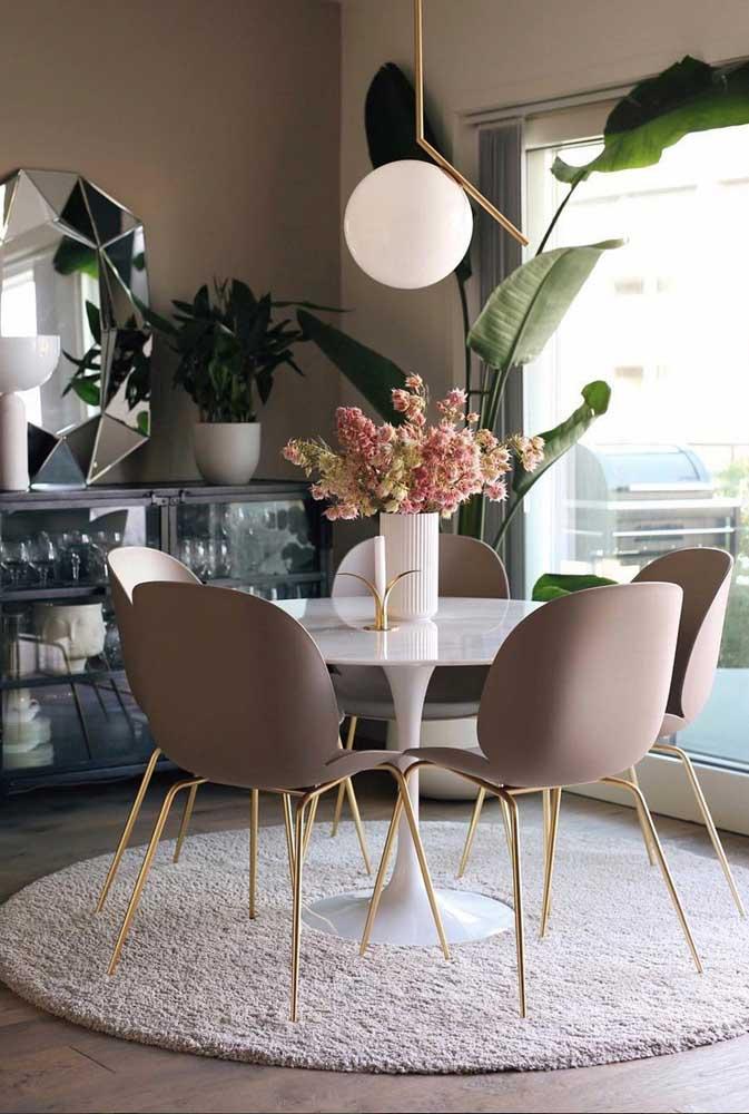 Decoração de sala de jantar com mesa redonda, tapete e buffet