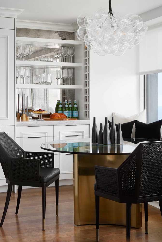 Decoração de sala de jantar pequena valorizada pelas cadeiras de design e pela luminária